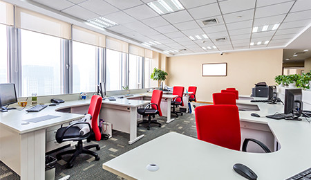 A very modern office with red chairs to make it pop